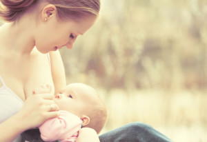 Woman breastfeeding infant in serene natural setting