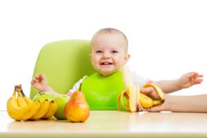 Happy baby smiling, eating fruit