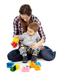 Child sitting in woman's lap playing with large interlocking blocks