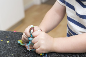 Young child playing with play dough