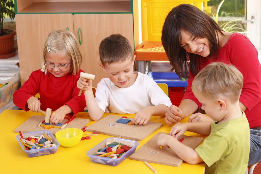 Smiling woman at a table with children playing