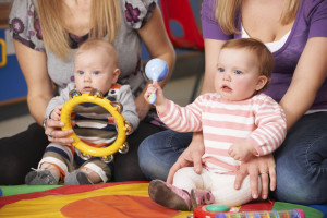 Babies and toddlers making music with tambourine and shaker