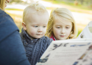 Two small children reading a book